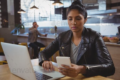 Woman with laptop using phone in cafe