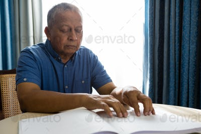 Senior man reading braille book in retirement home