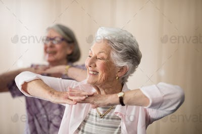 Smiling senior women with hands clasped looking away