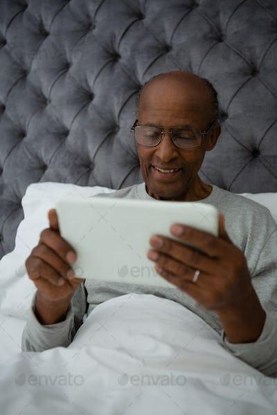 Senior man using digital tablet while resting on bed