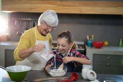 Grandmother adding water while granddaughter is mixing flour in a bowl