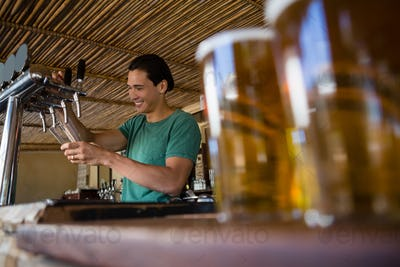 Close-up of beer glasses with bartender working at restaurant
