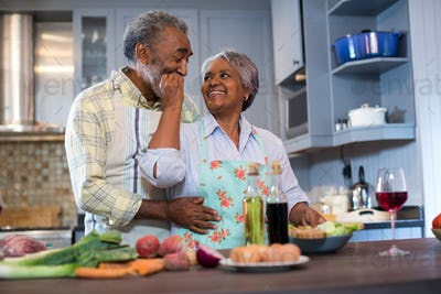 Affectionate senior couple preparing food