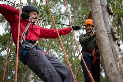 Young man wearing safety helmet crossing zip line while woman looking at him