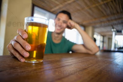 Man holding beer glass at bar counter