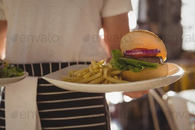 Mid section of waiter holding plate with burger and French fries