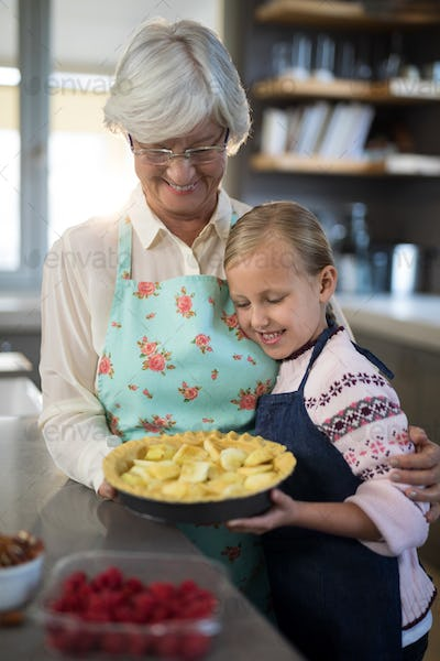 Grandmother and granddaughter looking at fresh cut apples on crust
