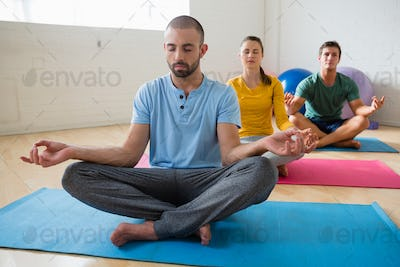 Yoga instructor with students meditating at club