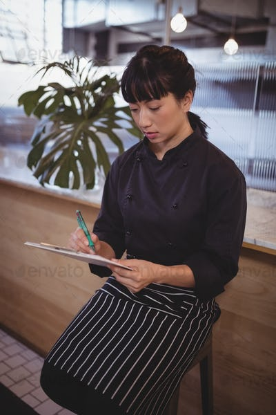 Young female waitress writing in clipboard while sitting on stool
