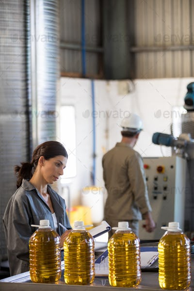 Female worker maintaining record while technician operating machine