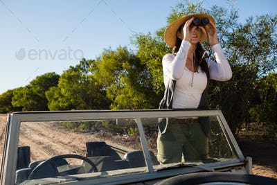 Young woman looking through binoculars standing in off road vehicle