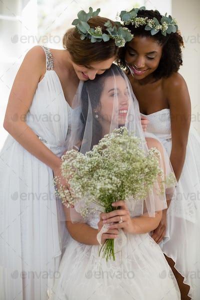 Bride interacting with bridesmaid at home