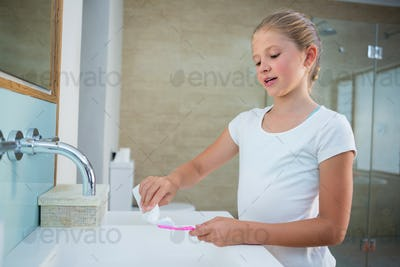 Girl removing toothpaste on brush