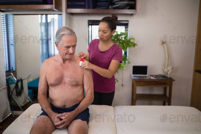 Female therapist applying elastic therapeutic tape on shoulder of shirtless senior male patient