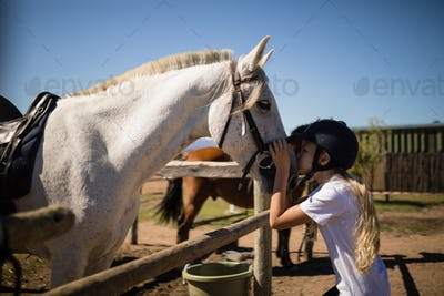 Girl kissing the white horse in the ranch