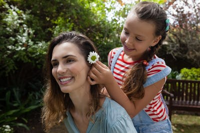 Girl positioning white flower in hair of mother
