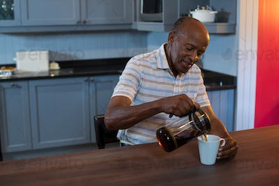 Senior man pouring coffee in cup