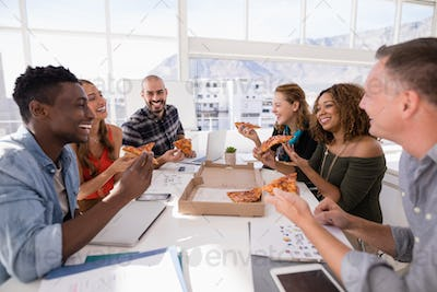 Happy executives sharing pizza in conference room
