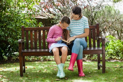 Mother and daughter reading novel while sitting on wooden bench