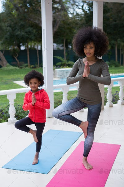 Mother and daughter performing yoga in the porch