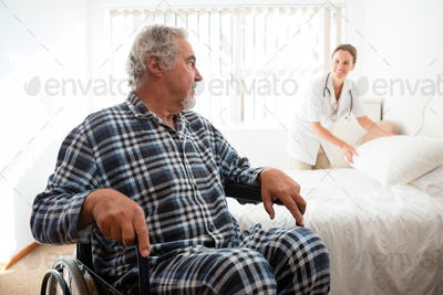 Senior man looking at doctor adjusting bed while sitting on wheelchair