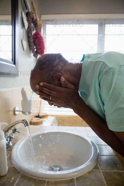Side view of senior man washing his face at sink