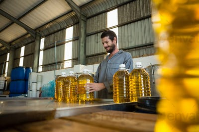 Worker examining a can of olive oil in factory