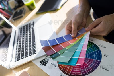 Female executives holding color shade swatch at her desk