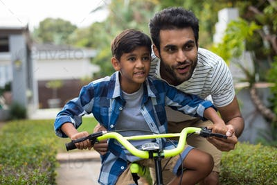 Father looking away while assisting son for cycling