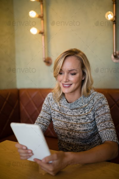Beautiful woman using digital tablet at table