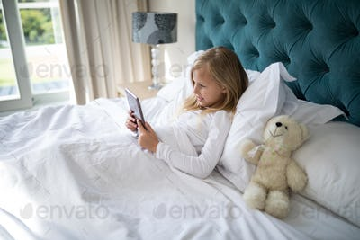 Girl using digital tablet while lying on bed