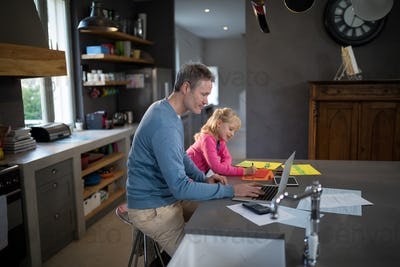 Father using a laptop while daughter is coloring