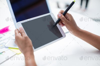 Hands of female graphic designer using graphic tablet at desk