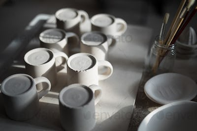 Close-up of ceramic mugs arranged on worktop