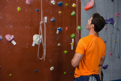 Rear view of young man looking up while standing by climbing wall