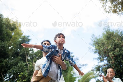 Low angle view of man looking at father playing with son