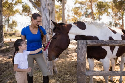 Woman assisting girl for cleaning horse