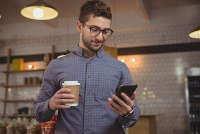 Businessman having coffee while using phone in cafe