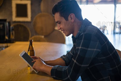 Side view of man using tablet at bar