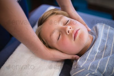 High angle view of boy with eyes closed receiving neck massage from female therapist