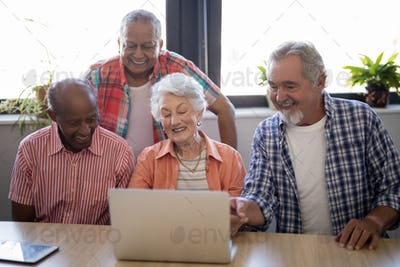 Happy senior people using laptop at table