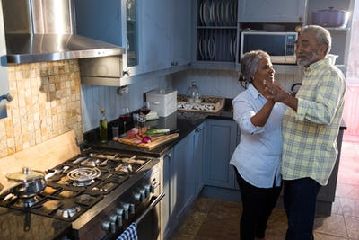 Smiling senior couple dancing in kitchen