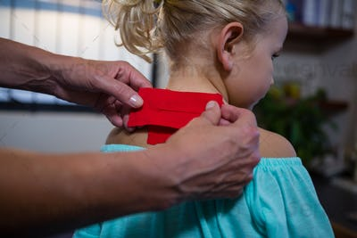Physiotherapist sticking tape on girl patient