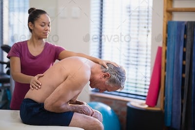 Young female therapist giving back massage to senior male patient bending on bed