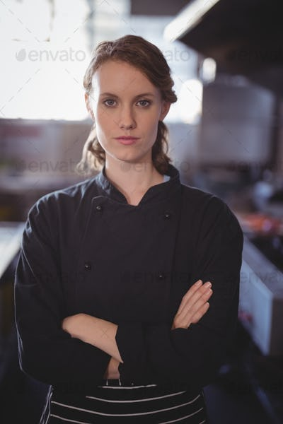 Portrait of confident young female barista standing with arms crossed