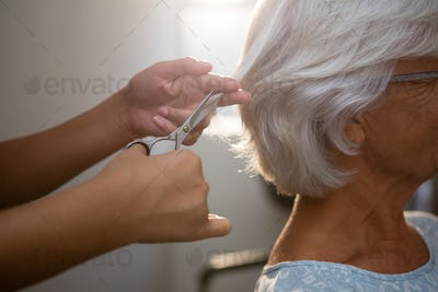 Cropped hands of beautician cutting hair of senior woman