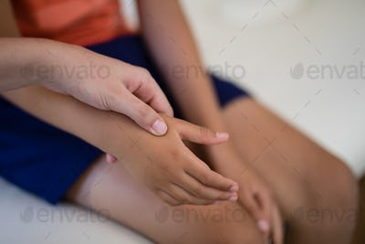 Close-up of female therapist examining hand while boy sitting on bed