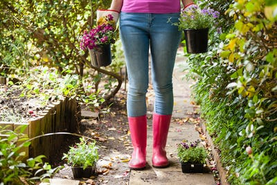 Low section of woman standing with potted plants on footpath