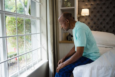 Side view of thoughtful senior man sitting on bed by window