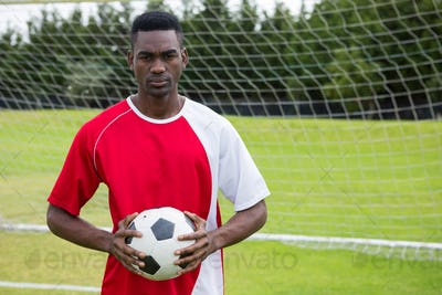 Portrait of serious confident male soccer player holding ball